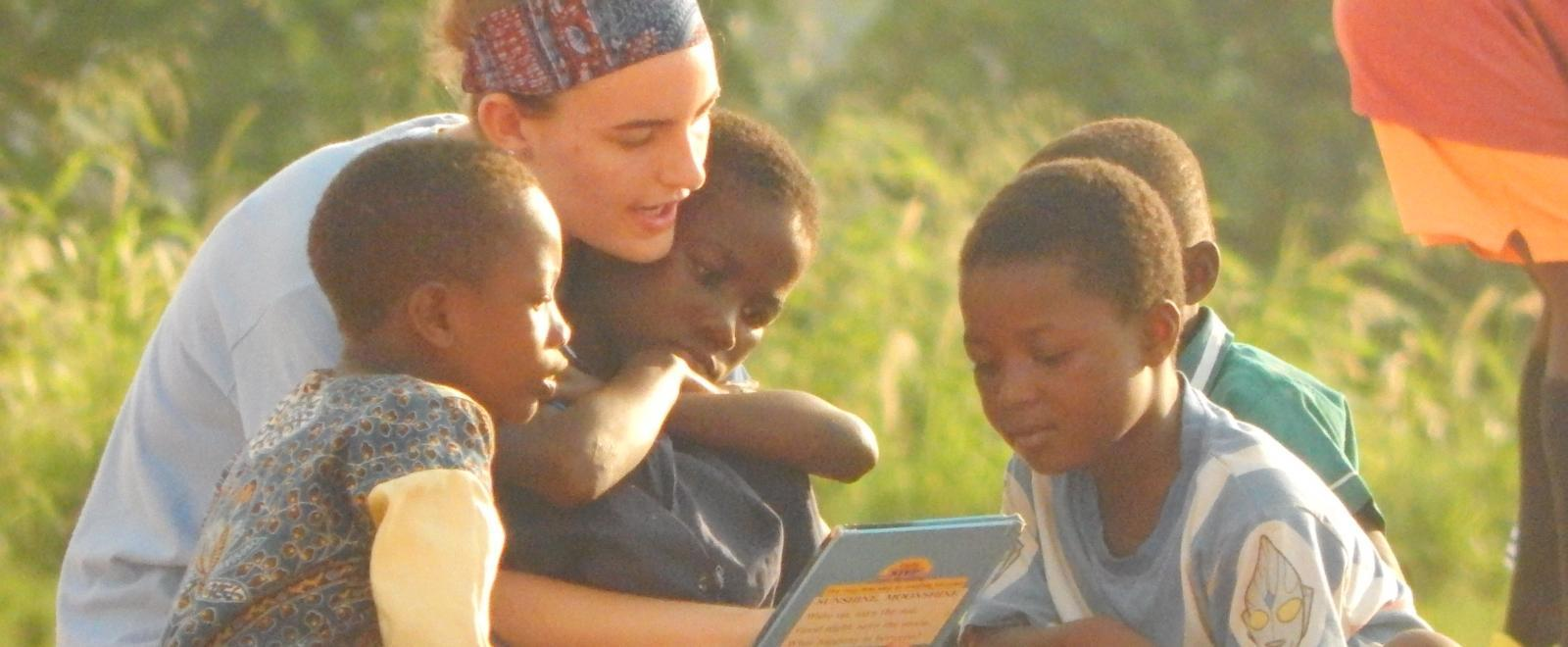 A volunteer with children in Ghana reads a book to a group of young students outdoors at her Childcare Project.